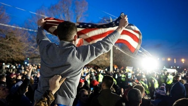 """FILE - In this Wednesday, April 6, 2016 file photo, a Donald Trump supporter waves a U.S. flag as he and others face off with anti-Trump protesters about 50 feet away, near the site of a campaign appearance by the Republican presidential candidate in Bethpage, N.Y. White men have suffered some real losses, even as they maintain advantages. """"What's made their lives more difficult is not what they think,"""" says Michael Kimmel, a Stony Brook University professor who studies masculinity and wrote the book """"Angry White Men."""" """"LGBT people didn't outsource their jobs. Minorities didn't cause climate change. Immigrants didn't issue predatory loans from which they now have lost their houses and everything they ever had. These guys are right to be angry, but they're delivering the mail to the wrong address."""" (AP Photo/Craig Ruttle)"""