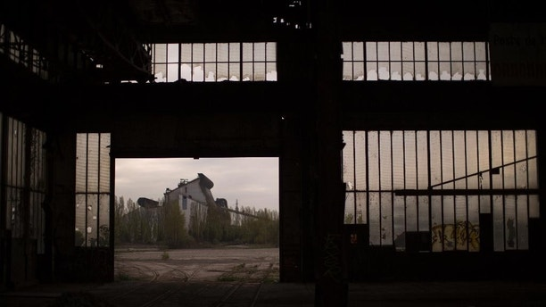 In this Thursday April 6, 2017 photo, a former steel factory is photographed through the gate of an abandoned industrial unit on the outskirts of Rombas, a french city located north east of France, near Hayange. In eastern France's industrial rustbelt, workers are massing behind the virulently nationalistic politics of populist Marine Le Pen. A large chunk of them will come from once left-leaning industrial towns like Hayange, scarred by the closure of its blast furnaces. (AP Photo/Emilio Morenatti)
