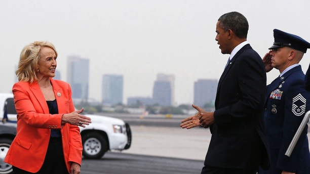 Arizona Governor Jan Brewer (L) waits to shake hands with U.S. President Barack Obama as he arrives aboard Air Force One, at Phoenix International Airport August 6, 2013. REUTERS/Larry Downing  (UNITED STATES - Tags: POLITICS) - GM1E987086P01