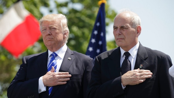 President Donald Trump (L) and U.S. Department of Homeland Security Secretary John Kelly hold their hands over their hearts for the U.S. National Anthem as they attend the Coast Guard Academy commencement ceremonies where Trump is addressing the graduating class in New London, Connecticut, U.S. May 17, 2017. REUTERS/Kevin Lamarque - HP1ED5H17DVCM