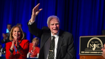 "FILE – In this April 22, 2014, file photo, former New Jersey Gov. Brendan Byrne waves as the audience sings him ""Happy Birthday"" and his wife Ruthi Zinn Byrne applauds, to mark his 90th birthday during the annual ""Congressional Dinner"" of the New Jersey State Chamber of Commerce in Washington, D.C. A ceremony at Healy's Tavern in Jersey City on Friday, March 16, 2018, will honor Byrne, who died in January at age 93. Byrne used to joke he wanted his ashes placed in Hudson County, known for its history of political shenanigans, so he could stay active in politics. (AP Photo/Cliff Owen, File)"