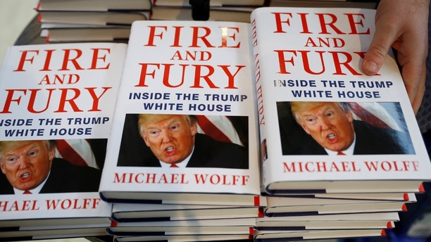 A shop worker arranges copies of Michael Wolff's book 'Fire And Fury' as they go on sale inside a branch of the Waterstones book store in Liverpool, Britain, January 11, 2018. REUTERS/Phil Noble - RC1BCA27F900