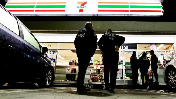 FILE - In this Wednesday, Jan. 10, 2018 file photo, U.S. Immigration and Customs Enforcement agents serve an employment audit notice at a 7-Eleven convenience store in Los Angeles. On Monday, March 19, 2018, the Southern California city Los Alamitos says it is planning to consider an ordinance to exempt itself from a state law that limits cooperation between local police and federal immigration agents. (AP Photo/Chris Carlson, File)