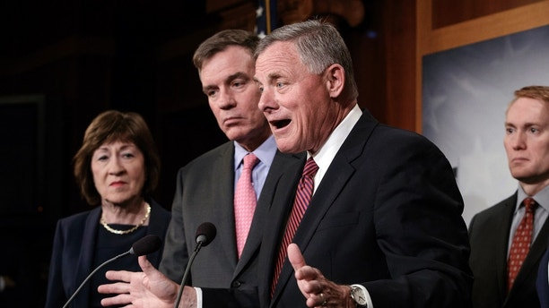 Senate Intelligence Committee Chairman Sen. Richard Burr, R-N.C., center, joined from left by, Sen. Susan Collins, R-Maine, Vice Chairman Mark Warner, D-Va., and Sen. James Lankford, R-Okla., previews some of the panel's recommendations for improving the nation's election infrastructure ahead of the 2018 midterm elections, during a news conference on Capitol Hill in Washington, Tuesday, March 20, 2018. On Wednesday, the committee will hold a hearing examining attempted hacks on state elections systems in 2016 and the federal and state response to those efforts. (AP Photo/J. Scott Applewhite)