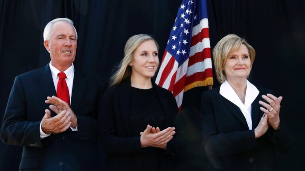 Mississippi Agriculture Commissioner Cindy Hyde-Smith, right, her husband, Mike Smith, left, and daughter Anna-Michael Smith applaud as Gov. Phil Bryant speaks about Hyde-Smith's qualifications as a former lawmaker, agriculture commissioner and rancher, before calling on her to succeed fellow Republican Thad Cochran in the U.S. Senate, Wednesday, March 21, 2018, in Hyde-Smith's hometown of Brookhaven, Miss. Cochran, who is 80, is stepping down April 1 because of poor health. (AP Photo/Rogelio V. Solis)