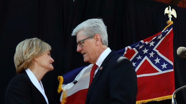 Mississippi Gov. Phil Bryant, congratulates state Agriculture Commissioner Cindy Hyde-Smith after appointing her to succeed fellow Republican Thad Cochran in the U.S. Senate, Wednesday, March 21, 2018, in Hyde-Smith's hometown of Brookhaven, Miss. Cochran, who is 80, is stepping down April 1 because of poor health. Hyde-Smith would be the first woman to represent Mississippi in Congress. She will immediately begin campaigning for a Nov. 6 nonpartisan special election to fill the rest of Cochran's term, which expires in January 2020. (AP Photo/Rogelio V. Solis)