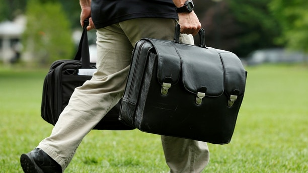 An aide for U.S. President Donald Trump carries a case which contains launch codes for the U.S. nuclear arsenal and which travels with the sitting U.S. president, before the president's departure from the South Lawn of the White House in Washington, U.S., June 17, 2017. REUTERS/Yuri Gripas - RC12194C0DF0