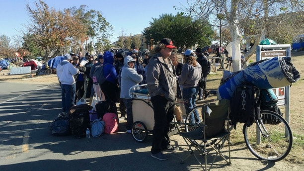 """FILE - In this Feb. 20, 2018, file photo, Homeless people line up in preparation to move from their homeless camp site along a riverbed in Anaheim, Calif. County officials in California have agreed to extend motel stays """"on a case-by-case basis"""" for hundreds of homeless people who were removed from tent camps along the Santa Ana River in February. The Los Angeles Times reports the decision came after a rare federal court hearing Saturday, March 17, 2018, and is the latest chapter of an extraordinary effort to help the growing numbers of homeless in one of America's wealthiest counties. (AP Photo/Amy Taxin, File)"""
