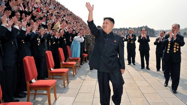 April 19: North Korean leader Kim Jung-Un waves as he arrives to take pictures with officials, creators and employees of the Mansudae Art Studio in Pyongyang.