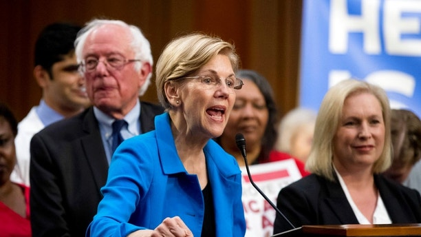 Sen. Elizabeth Warren, D-Mass., center, accompanied by Sen. Bernie Sanders, I-Vt., left, and Sen. Kirsten Gillibrand, D-N.Y., right, speaks during a news conference on Capitol Hill in Washington, Wednesday, Sept. 13, 2017, to unveil their Medicare for All legislation to reform health care. (AP Photo/Andrew Harnik)