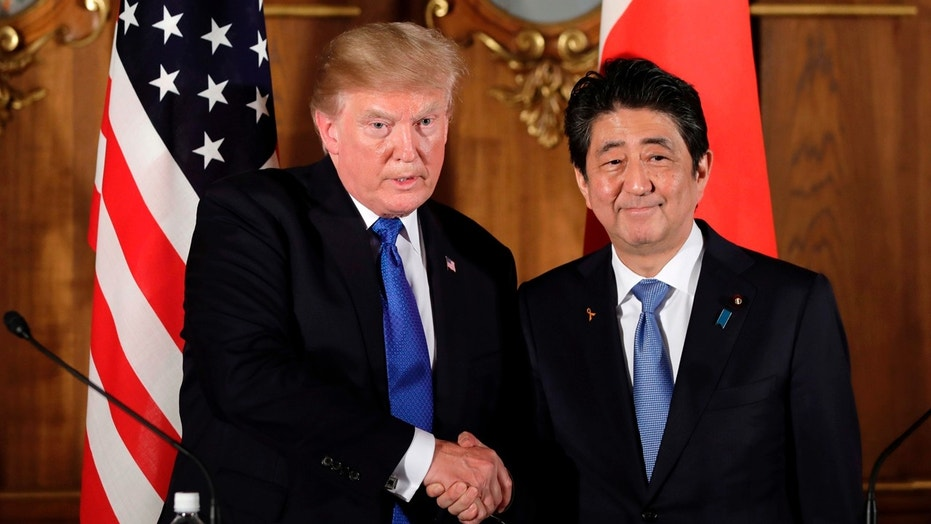 FILE - In this Nov. 6, 2017 file photo, President Donald Trump, left, shakes hands with Japanese Prime Minister Shinzo Abe during a joint news conference at the Akasaka Palace, in Tokyo.  Prime Minister Abe has announced plans to visit the U.S. from April 17-20, 2018, to discuss North Korea with President Trump ahead of expected summits between the North and the U.S. and South Korea. (Kiyoshi Ota/Pool Photo via AP, File)