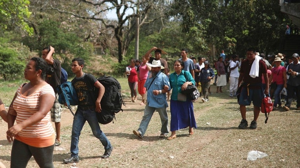 """Central American migrants arrive to a sports center during the annual Migrant Stations of the Cross caravan or """"Via crucis,"""" organized by the """"Pueblo Sin Fronteras"""" activist group, as the group makes a few-days stop in Matias Romero, Oaxaca state, Mexico, Monday, April 2, 2018.  The organized portions of the caravans usually don't proceed much farther north than the Gulf coast state of Veracruz, while some migrants, moving as individuals or in smaller groups, often take buses or trucks from there to the U.S. border. (AP Photo/Felix Marquez)"""