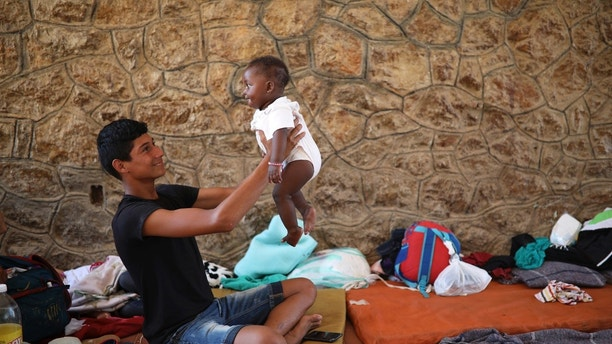 """A Central American migrant plays with a baby as they rest during a few-days stop of the annual Migrant Stations of the Cross caravan or """"Via crucis,"""" organized by the """"Pueblo Sin Fronteras"""" activist group, inside a sports center in Matias Romero, Oaxaca state, Mexico, Monday, April 2, 2018. A Mexican government official said the caravans are tolerated because migrants have a right under Mexican law to request asylum in Mexico or to request a humanitarian visa allowing travel to the U.S. border to seek asylum in the United States. (AP Photo/Felix Marquez)"""