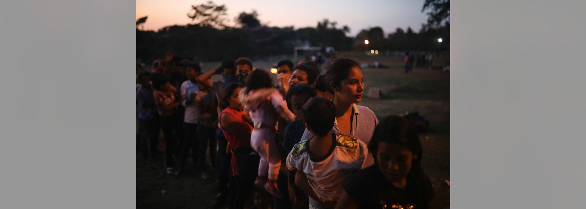 Central American migrant women and children stand in line for food during the annual Migrant Stations of the Cross caravan as the group sets up camp at a sports center in Matias Romero, Oaxaca state, Mexico, late Monday, April 2, 2018. The annual caravans have been held in southern Mexico for years as an Easter-season protest against the kidnappings, extortion, beatings and killings suffered by many Central American migrants as they cross Mexico. (AP Photo/Felix Marquez)