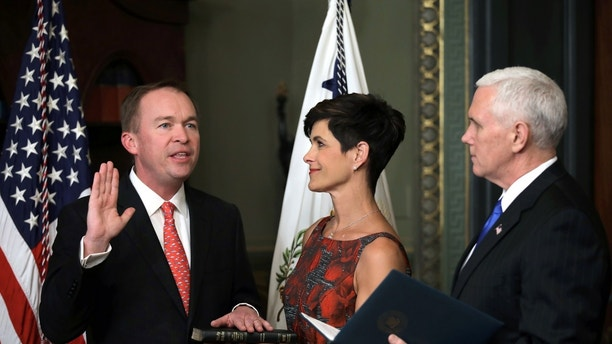 Office of Management and Budget Director Mick Mulvaney is sworn in by U.S. Vice President Mike Pence (R) as his wife Pamela holds a Bible during a ceremony at the executive office in Washington, U.S., February 16, 2017. REUTERS/Carlos Barria - RC16BBDE76F0