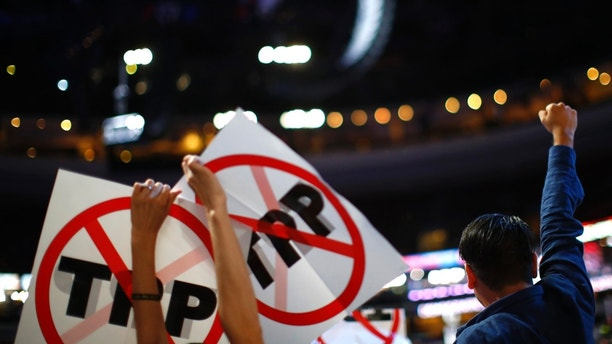 Delegates protesting against the Trans Pacific Partnership (TPP) trade agreement hold up signs during the first sesssion at the Democratic National Convention in Philadelphia, Pennsylvania, U.S. July 25, 2016. REUTERS/Carlos Barria - HT1EC7P1QJ6D9