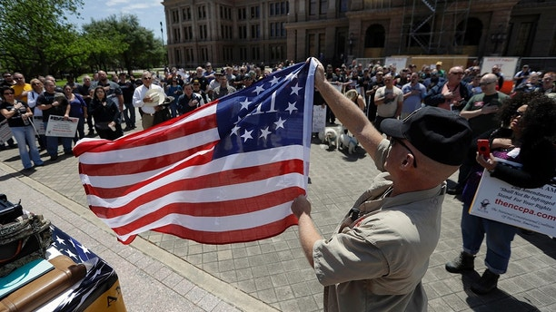 A man holds a 3% flag as a group recited the pledge during a pro gun-rights rally at the state capitol, Saturday, April 14, 2018, in Austin, Texas. Gun rights supporters rallied across the United States to counter a recent wave of student-led protests against gun violence. (AP Photo/Eric Gay)