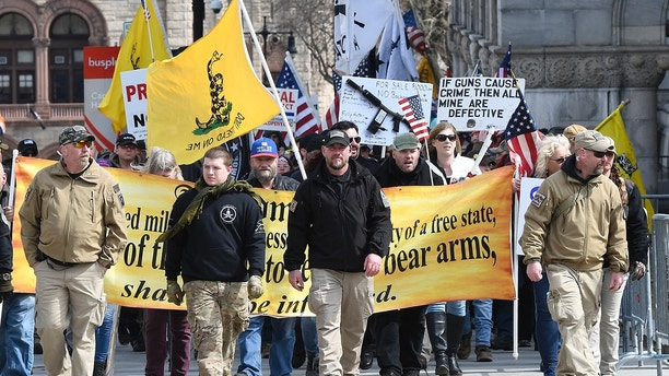 Gun rights activists with the National Constitutional Coalition of Patriotic Americans take part in a national rally aimed at pushing back against calls for stronger gun control measures outside the state Capitol Saturday, April 14, 2018, in Albany, N.Y. (AP Photo/Hans Pennink)