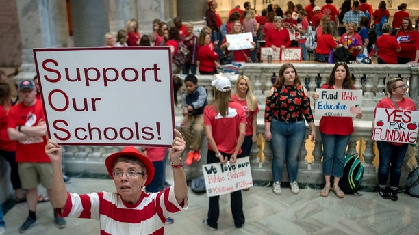 Karen Schwartz, a teacher at Phoenix School of Discovery in Louisville, stands outside the House chambers as Teachers from across Kentucky gather outside the state Capitol to rally for increased funding for education, Friday, April 13, 2018, in Frankfort, Ky. (AP Photo/Bryan Woolston)