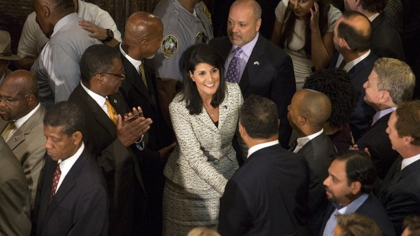 South Carolina Governor Nikki Haley is greeted at the state house before she sign the legislation on permanently removing the Confederate battle flag from the state capitol grounds, following an emotional debate spurred by the massacre of nine black churchgoers last month on Thursday in Columbia, United States, July 9, 2015. REUTERS/Jason Miczek - GF10000154277