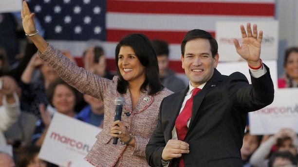 South Carolina Governor Nikki Haley (L) and U.S. Republican presidential candidate Marco Rubio (R) wave as they are announced on stage during a campaign event in Chapin, South Carolina February 17, 2016. Haley announced her endorsement of Rubio for the Republican presidential nomination. REUTERS/Chris Keane - GF10000313023