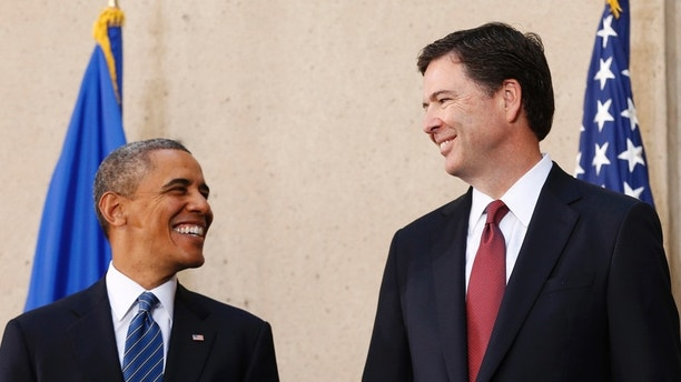 U.S. President Barack Obama (L) and new FBI Director James Comey smile during Comey's installation ceremony at the FBI Headquarters in Washington October 28, 2013. REUTERS/Kevin Lamarque  (UNITED STATES - Tags: POLITICS) - GM1E9AT04EZ01