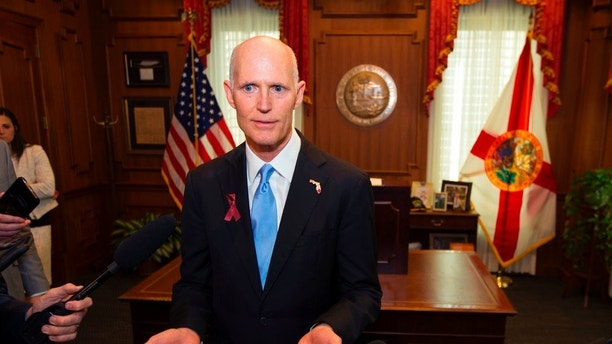 FILE- This March 9, 2018 file photo shows Florida Gov. Rick Scott talking to the media at the Florida Capital in Tallahassee, Fla. Attorney General Pam Bondi on Wednesday, April 4, 2018, appealed Judge Mark Walker's ruling to U.S. Court of Appeals for the Eleventh Circuit and asked that his order to overhaul the system by April 26 be put on hold. Gov. Scott and other Republican state officials are strongly defending the state's current system of restoring voting rights to ex-prisoners despite a federal judge's finding the system is flawed and potentially discriminatory. (AP Photo/Mark Wallheiser, File)