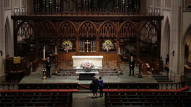 Mourners pause as former U.S. first lady Barbara Bush lies in repose during the visitation of former first lady Barbara Bush at St. Martin's Episcopal Church, Friday, April 20, 2018, in Houston. (AP Photo/David J. Phillip )