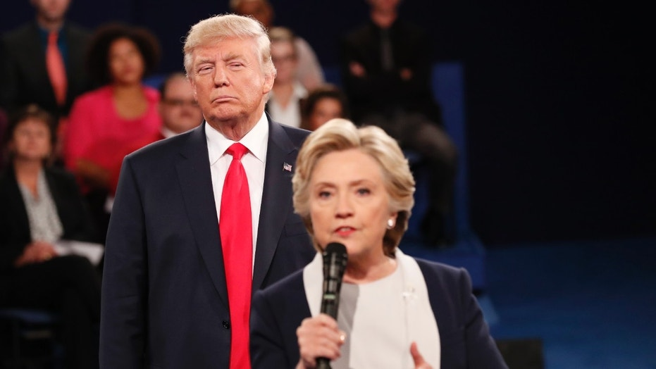 Oct. 9, 2016: Republican presidential nominee Donald Trump listens as Democratic nominee Hillary Clinton answers a question from the audience during their presidential town hall debate at Washington University in St. Louis.