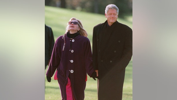 President and Mrs. Clinton walk to the White House after arriving by Marine One on the South Lawn Wednesday, Nov. 27, 1996, returning to Washington after a two-week trip to the Far East. The Clintons will depart for Camp David, Md., later today for the Thanksgiving holiday. Mrs Clinton is looking up at the upper floors of the White House. (AP Photo/Doug Mills)