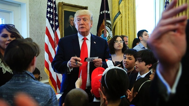 "President Donald Trump is surrounded by children in the Oval Office in celebration of ""Bring Our Daughters and Sons to Work Day"" at the White House in Washington, Thursday, April 26, 2018. (AP Photo/Manuel Balce Ceneta)"