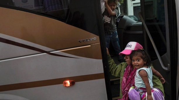 A Central American migrant and her children who are traveling with a caravan, arrive by bus to Tijuana, Mexico, Thursday, April 26, 2018. Caravans have been a fairly common tactic for years among advocacy groups to bring attention to Central American citizens seeking asylum in the U.S. to escape political persecution or criminal threats from gangs. (AP Photo/Hans-Maximo Musielik)