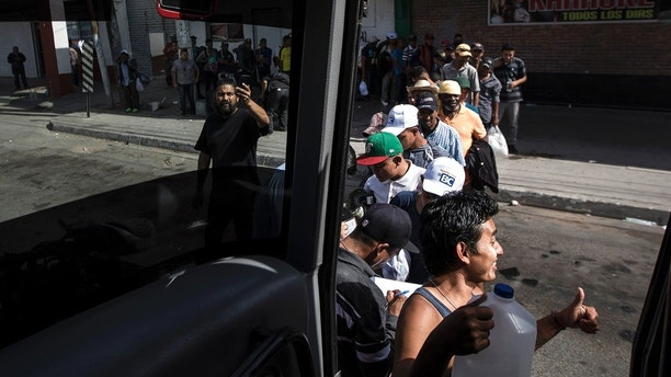 Migrants in a caravan of Central American asylum-seekers board a bus in Mexicali, Mexico, Thursday, April 26, 2018, for a two-hour drive to Tijuana to join up with about 175 others who already arrived. Lawyers planned free workshops on the U.S. immigration system on Friday and Saturday as many planned to seek asylum starting Sunday at San Diego's San Ysidro border crossing, the nation's busiest. (AP Photo/Hans-Maximo Musielik)