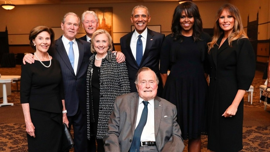Former President George H. W. Bush, center, with First Ladies Melania Trump, far right, Michelle Obama, right, Former President Barack Obama, upper center, former Secretary of State Hillary Clinton, left, former Presidents Bill Clinton and George W. Bush, and former First Lady Laura Bush pose for a photo at the funeral of former First Lady Barbara Bush.