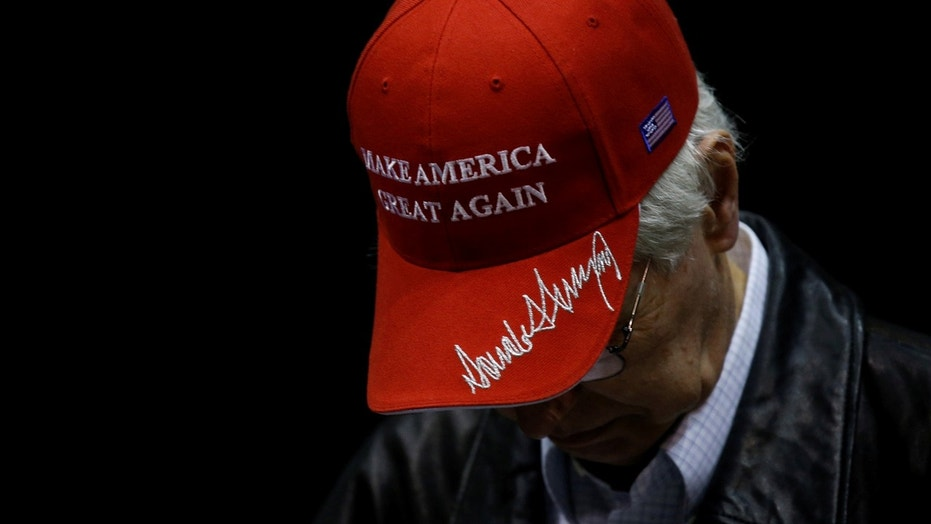 FILE:A man wears a hat embroidered with U.S. President Trump's signature at a Trump rally Nashville.