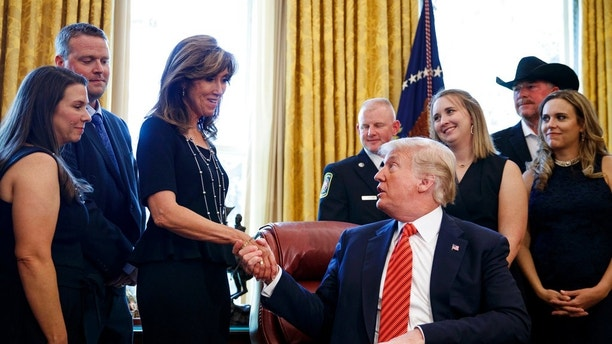President Donald Trump shakes hands with pilot Tammie Jo Shults as he meets with crew and passengers of Southwest Airlines Flight 1380 in the Oval Office of the White House in Washington, Tuesday, May 1, 2018. (AP Photo/Carolyn Kaster)