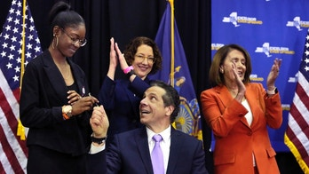 New York Gov. Andrew Cuomo hands a pen to Marjory Stoneman Douglas High School student Aalayah Eastmond, left, as he signs a bill at John Jay College of Criminal Justice, that removes guns from domestic abusers, Tuesday, May 1, 2018, in New York. Joining the ceremony are Amy Barasch, background center, Executive Director of Her Justice, and U.S. Rep. Nancy Pelosi, D-Calif. (AP Photo/Richard Drew)