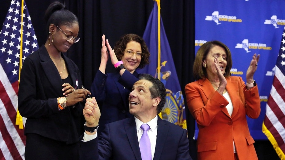 New York Gov. Andrew Cuomo, D, hands a pen to a survivor of the Parkland school shooting after he signs a bill that removes guns from domestic abusers. House Minority Leader Nancy Pelosi (right) attended the bill signing.