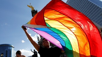 A member of the LGBT community, holds up a rainbow flag during a protest against the constant discrimination and violence against their community, at the Angel of Independence monument in Mexico City, Mexico June 23, 2017. REUTERS/Henry Romero - RC1FC06C6FD0
