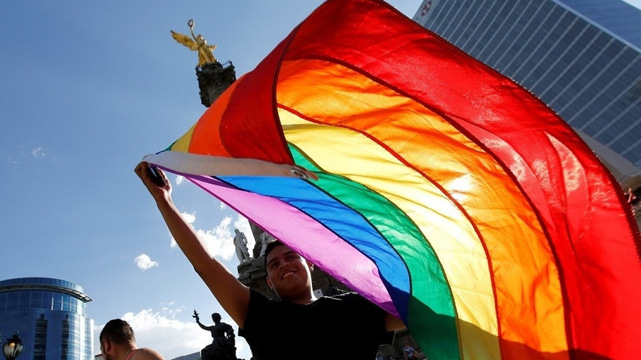 A member of the LGBT community, holds up a rainbow flag during a protest against the constant discrimination and violence against their community, at the Angel of Independence monument in Mexico City, Mexico June 23, 2017