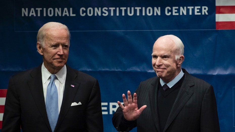 Sen. John McCain, R-Ariz., right, accompanied by Chair of the National Constitution Center's Board of Trustees, former Vice President Joe Biden, waves as he takes the stage before receiving the Liberty Medal in Philadelphia, Monday, Oct. 16, 2017.
