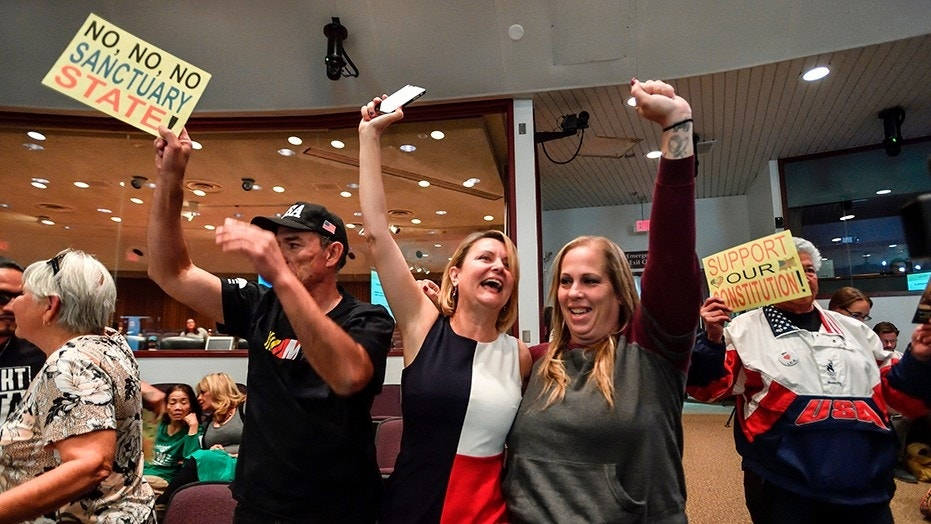 David Hernandez, left, Genevieve Peters, center, and Jennifer Martinez celebrate after the Orange County Board of Supervisors voted to join the U.S. Department of Justice lawsuit against the State of California's sanctuary cities law, March 27, 2018.
