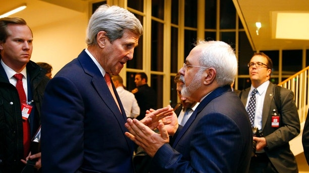 FILE - In this Jan. 16, 2016 file-pool photo, Secretary of State John Kerry talks with Iranian Foreign Minister Mohammad Javad Zarif in Vienna, after the International Atomic Energy Agency verified that Iran has met all conditions under the nuclear deal. President Donald Trump is weighing whether to pull the U.S. out of Iran's nuclear deal, a 2015 agreement that capped over a decade of hostility between Tehran and the West over its atomic program. (Kevin Lamarque/Pool via AP, File)
