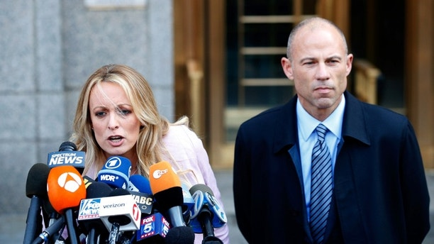 Adult film actress Stephanie Clifford, also known as Stormy Daniels, speaks to media along with lawyer Michael Avenatti (R) outside federal court in the Manhattan borough of New York City, New York, U.S., April 16, 2018. REUTERS/Brendan Mcdermid - HP1EE4G1MU9NV