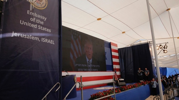 U.S. President Donald Trump is seen on screen as he delivers his speech during the opening ceremony of the new U.S. embassy in Jerusalem, Monday, May 14, 2018. Amid deadly clashes along the Israeli-Palestinian border, President Donald Trump's top aides and supporters on Monday celebrated the opening of the new U.S. Embassy in Jerusalem as a campaign promised fulfilled. (AP Photo/Sebastian Scheiner)