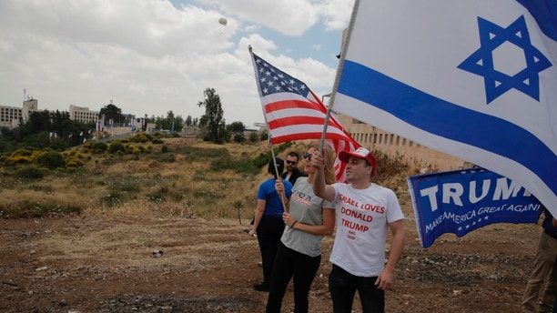 Israelis hold American and Israeli flags with the new U.S. embassy in the background in Jerusalem, Monday, May 14, 2018. Israel prepared for the festive inauguration of a new U.S. Embassy in contested Jerusalem. (AP Photo/Sebastian Scheiner)