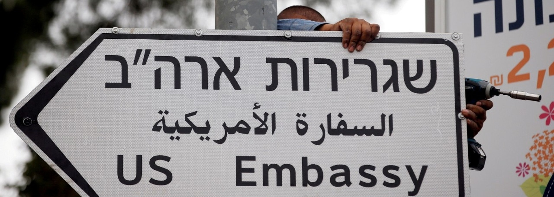 FILE PHOTO: A worker hangs a road sign directing to the U.S. embassy, in the area of the U.S. consulate in Jerusalem, May 7, 2018. REUTERS/Ronen Zvulun/File Photo - RC144B4FBA30
