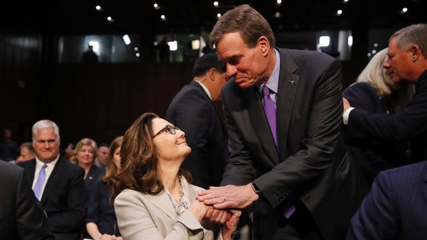 CIA nominee Gina Haspel is greeted by Senate Intelligence Committee Vice Chairman Mark Warner, D-Va., before a confirmation hearing of the Senate Intelligence Committee on Capitol Hill, Wednesday, May 9, 2018 in Washington. (AP Photo/Alex Brandon)