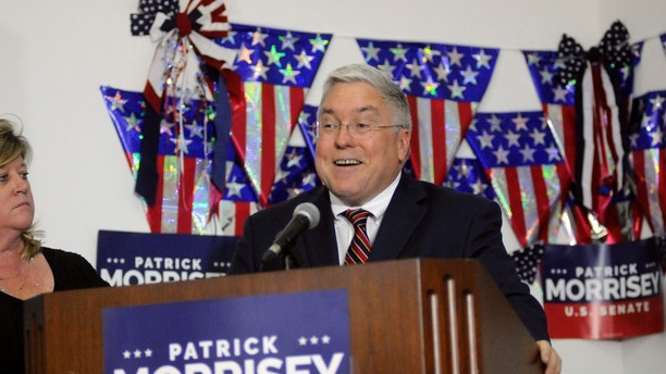 Denise Morrisey stands next to her husband, West Virginia Attorney General Patrick Morrisey, as he speaks at his campaign headquarters Tuesday, May 8, 2018, in Kearnesville, W.Va. (Ron Agnir/The Journal via AP)