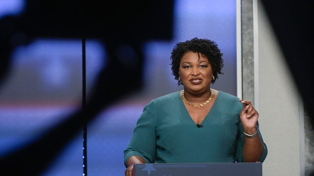 Georgia Democratic gubernatorial candidate Stacey Abrams participates in a debate with Stacey Evans as a stage manager holds up a time card Sunday, May 20, 2018, in Atlanta. (AP Photo/John Amis)